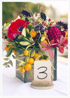 modern & rustic centerpiece, all at the same time - love the old fashioned pin frog as a table number holder.