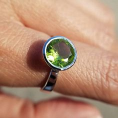 This beautiful Peridot solitaire ring has a round sparkling genuine peridot crystal set in sterling silver. Youll love the natural green color of this August birthstone crystal ring. Features an open back design so that the Peridots green color rays can penetrate your skin for energetic healing.  Ring Size: See availability on drop down. Setting: 925 sterling silver  → 0.39 x 0.39 x 0.24 (10mm x 10mm x 6mm) → Band width at the bottom is 0.16 (4mm) → Genuine untreated peridot crystal  Peridot…