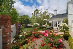Traditional rose gardens and landscaping, plus mature trees and foliage, are the perfect complements to the home's classic Paul Williams design.