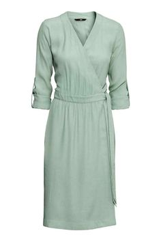 Sukienka kopertowa: Kopertowa sukienka z tkaniny z wiązaniem z boku. Długie rękawy z patką i guzikiem. Bez podszewki.
