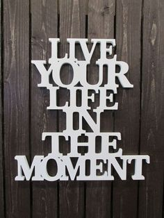 Puutaulu. Teksti: Live your life in the moment.
