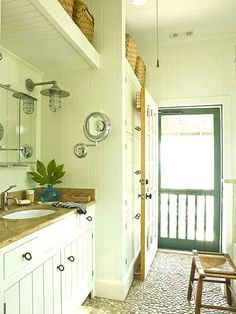 Off-white bead-board walls, river-rock floors and a cottage style screen door add cozy charm to this master bathroom. myhomeideas.com