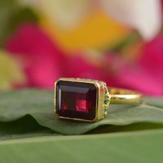 This stunning one of a kind ring has been handmade in our workshops. It has a 9.85ct rubellite which is surrounded by emeralds. The ring is made in 18ct gold.  Dimensions 15mm x 12mm  UK size O/ USA size - 7 1/4  The ring can be resized on request.  Alternative Wedding Jewellery, Alternative Engagement Rings, Hand Engraving, Anniversary Gifts, Gemstone Jewelry, Emeralds, Gemstones, Silver, Gold
