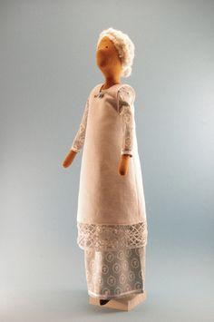 Greta trägt ein einfaches Hauskleid und eine Schürze mit Spitze, wie sie um die Jahrhundertwende in Mode war.    Ihr wollenes Haar ist fest am Kopf mi