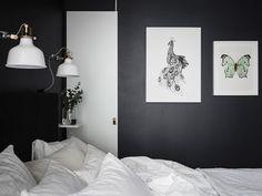 Deși în mod normal finisajele în negru înghesuie vizual spațiul, în acest dormitor, tavanul înalt și detaliile în alb reușesc să tran...