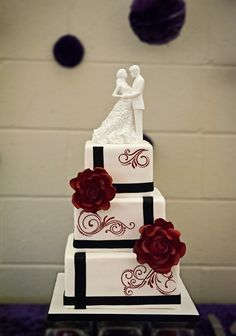 Square Wedding Cakes - A cake doesn't always need lots of flowers all over it. Sometimes one or two large ones can make a big impact. Calvin and Amanda wanted a simple black and white design for their wedding cake, embellished with red flourishes. Two large roses were added for a pop of colour and to complement the rose detail on the Monique Lhuillier cake topper that the bride provided.
