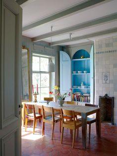 La couleur gris clair des poutres répond à celle des murs, en carrelage et en bois, joue avec le bleu du placard et l'ocre des tomettes.