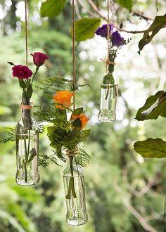 Mesmo quem não tem árvore em casa pode usar as garrafas com flores pendurando cada uma com ganchinhos no teto