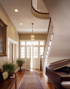 Foyer entry under the stairs. Light and bright entry, transom window, ferns...