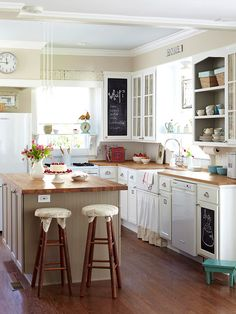I really like this kitchen. The white cabinets are cute and feature nice hardware; the chalkboards are both functional and stylish; the wood counter tops add nice color and texture; and I adore the island.