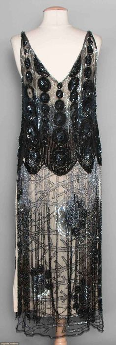 "Sequined & Beaded Tabard, C. 1925. Black net, shoulder to hip area covered w/ black & gunmetal sequins in dense circular patterns, stylized branch & blossom pattern below hip to hem is partially concealed by 20+"" long beaded fringe. Suddon-Cleaver Costume Collection (hva)"