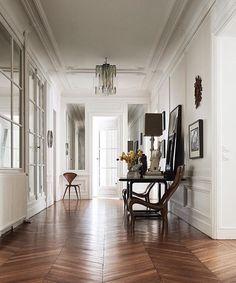 herringbone wood floors and mouldings on the walls lovely white hallway
