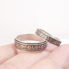 These rings feature a raised petunia pattern at their center. The five-petaled flowers weave their way around the band connected by a leafy vine. The wider ring measures 6mm wide (1/4). The narrower band measures 4mm wide (5/32). These rings are made of pure sterling silver and