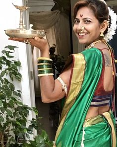 A young woman holds a Diwali diya thali and is dressed for the part! Cheap Flights To India, Diwali Photos, Diwali Diya, Discount Travel, Photo Contest, Sari, Indian, Woman, Dresses