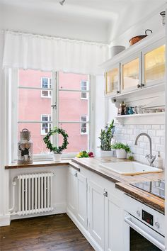 white vintage kitchen--super cute. Green wreaths make everything cuter!