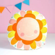 Uma flor feliz que fará miúdos e graúdos sorrir sempre!  A almofada é feita em tecido de qualidade 100% algodão. Esta almofada redonda mede 23×23 cm. Macia, robusta e alegre - esta almofada é um objecto diferente para enfeitar a caminha do seu bebé. O acabamento no verso pode variar (tecidos lisos ou com padrão).Ilustrações originais de PinkNounou.