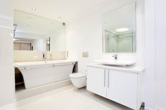 All-white bathroom with two large mirrors