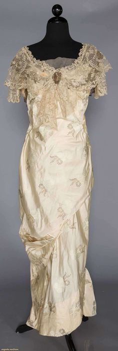 VORY BROCADE EVENING GOWN, NEW YORK, c. 1912 Empire gown of ivory silk brocaded w/ metallic gold & pale blue flowers, draped columnular silhouette, Brussels applique lace bodice