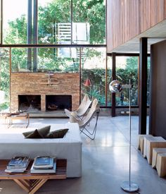 Dwell  |  The living room resembles a Sticotti furniture showroom: The architect designed the couch, coffee tables, and stumplike stools. The fireplace is made of stacked stone from San Juan, a nearby province.