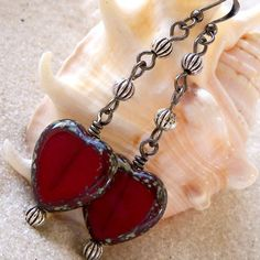 This listing is for a pair of long, glass beaded, heart earrings. These are deep crimson red beads with a Picasso finish. They measure 15x15mm