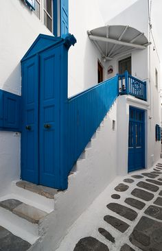 Streets of Hora - Mykonos, Greece. Blue stair railings. Blue doors. White buildings. Stone street.