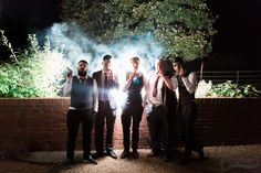 October wedding. Groom and friends celebrate with cigars, backlit outside New Guesten Hall at Avoncroft Museum of Historic Buildings (avoncroft.org.uk). Jay Emme Photography.