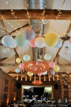 Gathered fairy light canopy with pastel paper lanterns for a spring wedding lighting scheme at Wasing Park barn