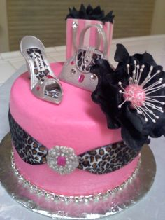 Bling/Fashionista Birthday - Chocolate fudge cake with chocolate ganache filling and buttercream icing. Shoe, purse, shopping bag, brooch and flower are all made of gumpaste. Painted all with silver shimmer dust. Added non-edible jewels and leopard print ribbon. String of rhinestones for the bottom border. Cupcakes are chocolate fudge iced with buttercream then covered with embossed fondant. Gumpaste flowers with sugar pearls and royal icing swirls and dots.
