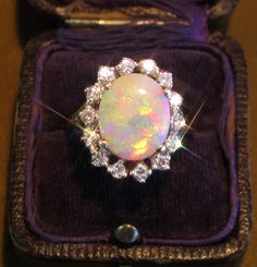 HUGE VINTAGE SOLID OPAL & DIAMOND RING!! VERY FINE DIAMONDS AND NATURAL 2.25 CARAT LIGHTNING RIDGE OPAL!!! ANTIQUE BEAUTIFUL SPARKLING WHITE DIAMONDS & GLOWING OPAL in Rich 14k White Gold . Pretty colors,,Peach/ Red/ Gold/ Blue/ Green/ Purple. Lots of Rainbow Fire!! This One is Gorgeous,,,,,Fine Natural Shimmering Opal & over a Half Carat of Diamonds,,,,Stunning!! Beautifully kept in a Vintage Royal Blue Velvet Box with Blue Velvet Plush and Ivory Silk Interior.