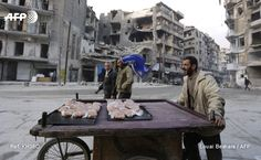 A Syrian man sells croissants in Aleppo's formerly rebel-held al-Shaar neighbourhood on January 21, 2017, a month after government forces retook the northern Syrian city from rebel fighters. LOUAI...