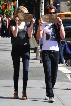 """Emma Stone and Andrew Garfield -- the signs read: """"We just found out that there are paparazzi outside the restaurant we were eating in, so why not take this…"""" and """"Opportunity to bring attention to organizations that need and deserve it? www.wwo.org and www.gildasclubnyc.org, Have A Great Day!"""""""