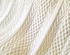 This is the pattern for the Celtic Aran Afghan I created while I was planning a trip to Ireland. It was knit in the weeks leading up to the trip, during the trip and in the few weeks after coming home. Everytime I look at it I have wonderful memories of that exciting time and I will treasure it for years to come. I hope you do too.  The finished blanket is approximately 60 wide by 72 long, plus an 8 Triple Knot Fringe at each end. It is made up of 5 panels knitted separately and then seamed…