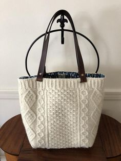 This large tote bag is constructed from a traditional Irish Aran cable knit repurposed felted sweater and two brown leather belts. The exterior is made of a cable knit wool sweater I felted myself. The lining is made from 100% cotton fabric. The two belts, while different, are not noticeably so when Crotchet Bags, Knitted Bags, Brown Leather Belt, Leather Belts, Homemade Bags, Sweet Bags, Handmade Handbags, Crochet Handbags, Casual Bags