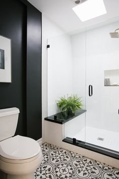 Contemporary Bathroom: Clear glass doors and small vibrant plant in black and white bathroom..