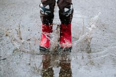 red boots splashing in rain puddle by Brian Powell