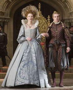 """- 10. 5 - RENACIMIENTO - En la última etapa del primer periodo del Renacimiento, vemos que los calzones siguen igual,  y la única novedad es la intrudución de cuellos y cuerpo aballenado y rígido.  En la imagen podemos ver una escena de la película """"Elizabeth la edad de oro"""", inspirada en la reina de Inglaterra Isabel. Podemos observar que el hombre que está al aldo de la reian lleva unos haut de chausses largos, con cuchilladas para crear volumen."""