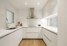 Bianca e dalle linee pure e definite, la cucina dell'appartamento di Barcellona è piccola, ma ben organizzata. Una finestrella rettangolare sul lato del piano di lavoro affaccia alla sala, creando una relazione visiva immediata
