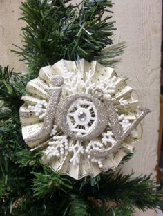 vintage sheet music rosette embellished with Dollar Tree snowflake and JOY ornaments