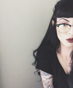 Cateye glasses, chestlength black hair, black tee, & mauve lips