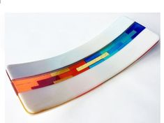 This unique rectangular fused glass tray will grace any room and can be used for display or to serve sushi, fruits, finger foods, and appetizers. It is made of muticolored layers of transparent glass framed by opaque white glass. The glass is hand cut, assembled, fused at 1490 F in a glass kiln, then cold worked and slumped into a mold to achieve its final shape. Some designed require multiple firing. Dimensions: 15X52 Weight: 3 lbs Made of food safe Bullseye Glass Please hand wash. Not…
