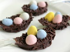 Dip a spoon in melted chocolate, and set on parchment or wax paper. Add three candy eggs, then scatter chocolate sprinkles to make the nest. Read more: http://www.rd.com/slideshows/easter-crafts/#ixzz3NOQdg2qn