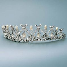 A dainty diamond and natural pearl tiara, by Garrard. Designed as a series of diamond 'Greek Lyre' motifs, each 'lyre' having a suspended diamond foliate ending in a pearl, with smaller diamond spacers, topped with pearls. Gold Tiara, Diamond Tiara, Diamond Cuts, Royal Tiaras, Tiaras And Crowns, Vintage Headbands, Royal Jewelry, Jewellery, Royals