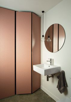 A pegboard screen painted in a salmon hue is a clever way to hide a bathtub and wash basin, as shown in this New Zealand bathroom. This originally appeared in A Dramatic Cutout Wall and Other Surprises Define This Playful House.