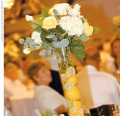 At the reception, the color yellow helped set the tone for a lively, beautifully turned-out evening. The centerpieces combined cut-up lemons and limes with white hydrangea and yellow roses in tall glass vases; the lemon-flavored wedding cake was heaped wi...
