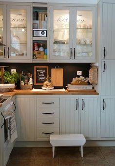 white glass cabinets, dark backsplash, butcher block
