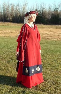 This gown was constructed of red wool flannel and lined with blue silk.  It is in the Italian/Southern European style late style. Worn with a supportive under kirtle and a stuffed roll headdress created from a linen roll, wrapped in burgundy silk and banded with velveteen and pearl strips. I love this, simple, elegant and comfy!