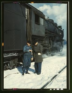 "From the Library of Congress. Caption is ""Atchison, Topeka, and Santa Fe railroad conductor George E. Burton and engineer J.W. Edwards comparing time before pulling out of Corwith railroad yard for Chillicothe, Illinois"". March 1943"