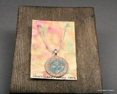 fleur de lis and zodiac ceramic pendant with silver snake chain by Hurricane Pottery.