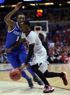 Russ Smith #2 of the Louisville Cardinals drives to the basket against James Young #1 of the Kentucky Wildcats during the regional semifinal...