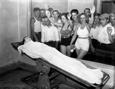 This is a genuine photo of a deceased John Dillinger, for some reason with two women in bathing suits leaning up against the glass to view him along with a crowd of men. Can only suppose it was a hot day at the morgue